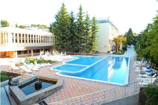 Просторный бассейн с обустроенной релаксационной зоной во внутреннем дворе отеля