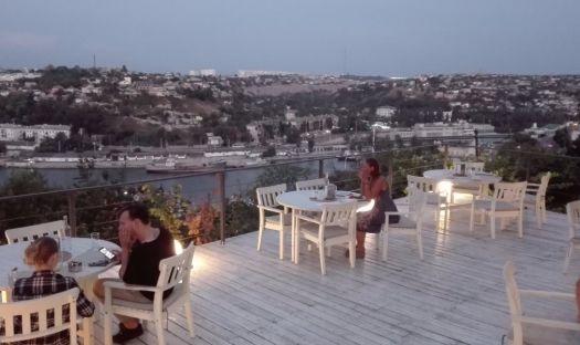 Ужин на террасе ресторана Остров с видом на море и огоньки вечернего города напоминает вечер в изысканом ресторане Италии