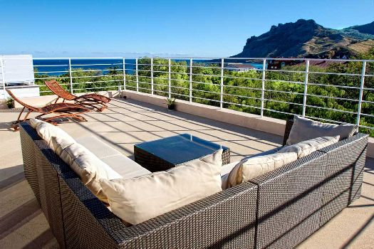 Терраса в двухуровневом номере с шезлонгами для принятия солнечных ванн
